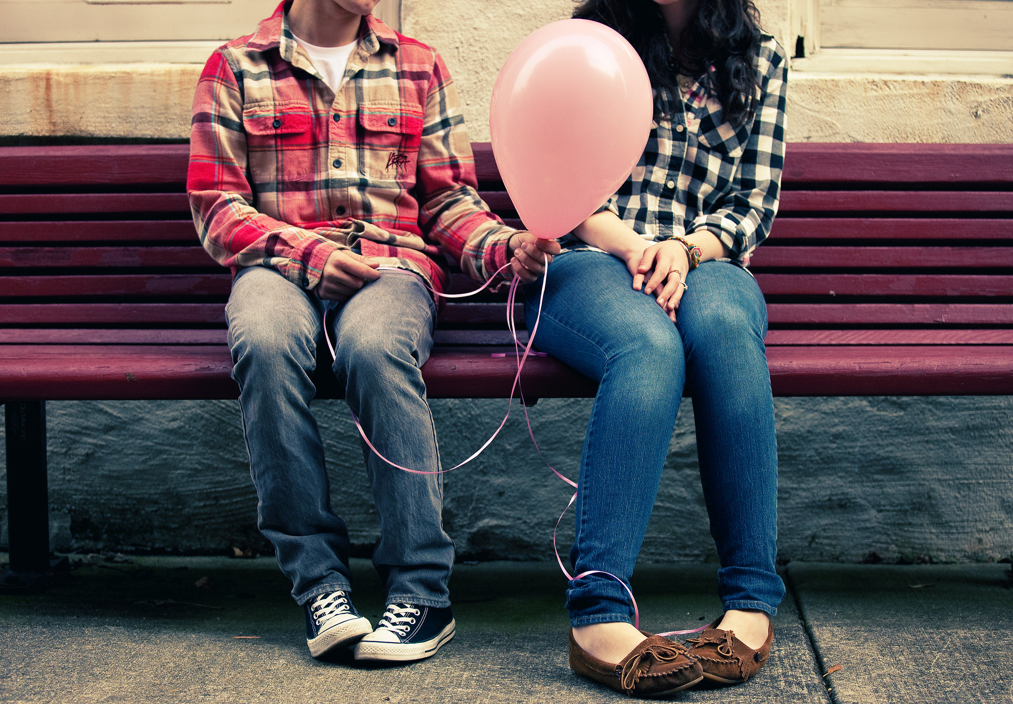 Two people sitting on a bench, each with shy body language, one offering to give the other a balloon