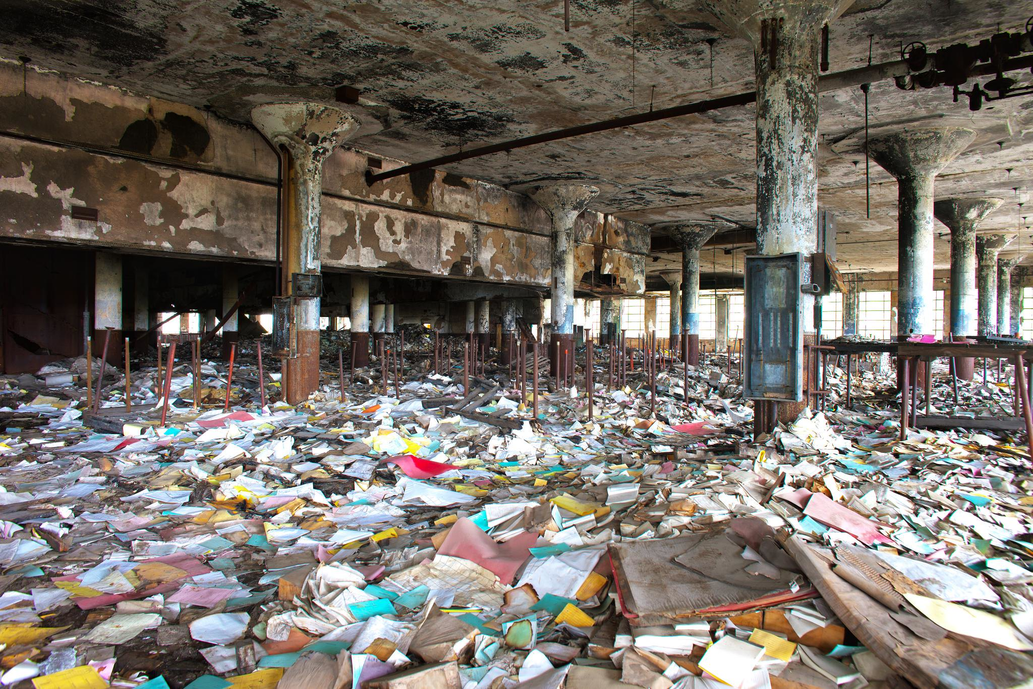 Abandoned warehouse, floor covered with books and papers strewn all around.