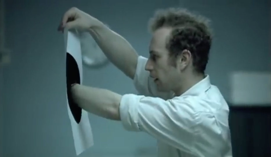 An innocent office worker accidentally creates an black hole on paper that he can reach into. ACME, eat your heart out.