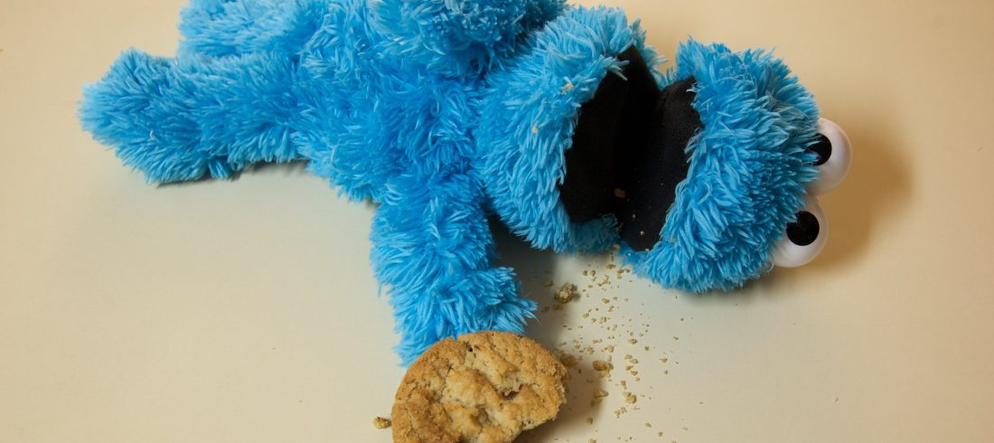 plush Cookie Monster lying on its back, apparently dead, cookie with one bite taken out left at tip of outstretched hand
