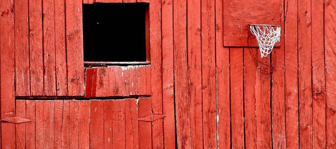 A red-painted wooden wall, likely the side of a barn. What's inside that gap?