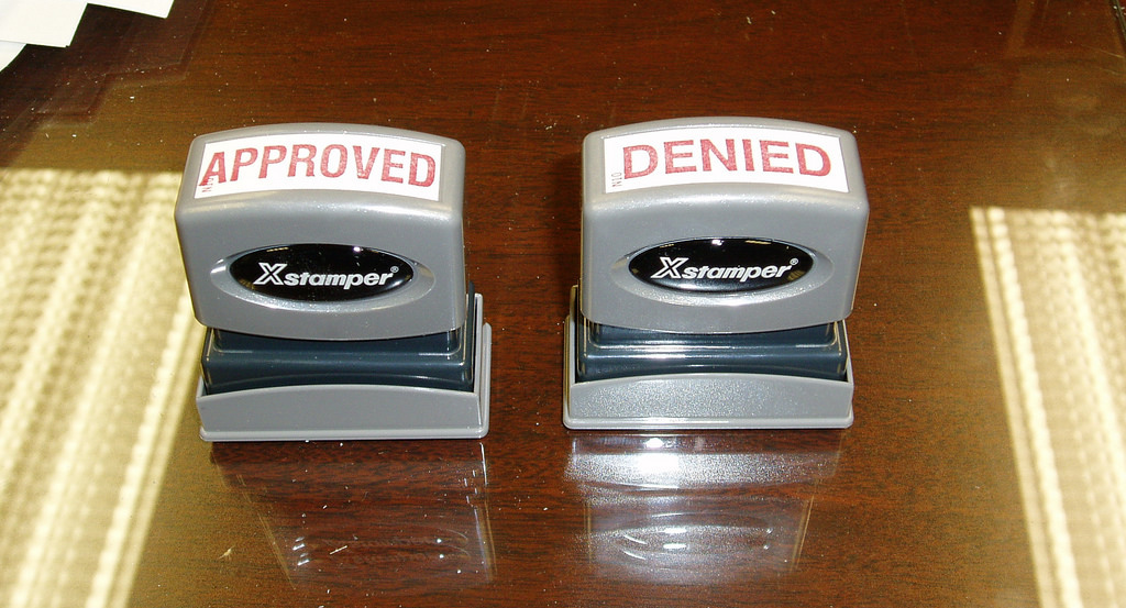 "standard office stamps on desk; one reads ""APPROVED""; the other, ""DENIED"""