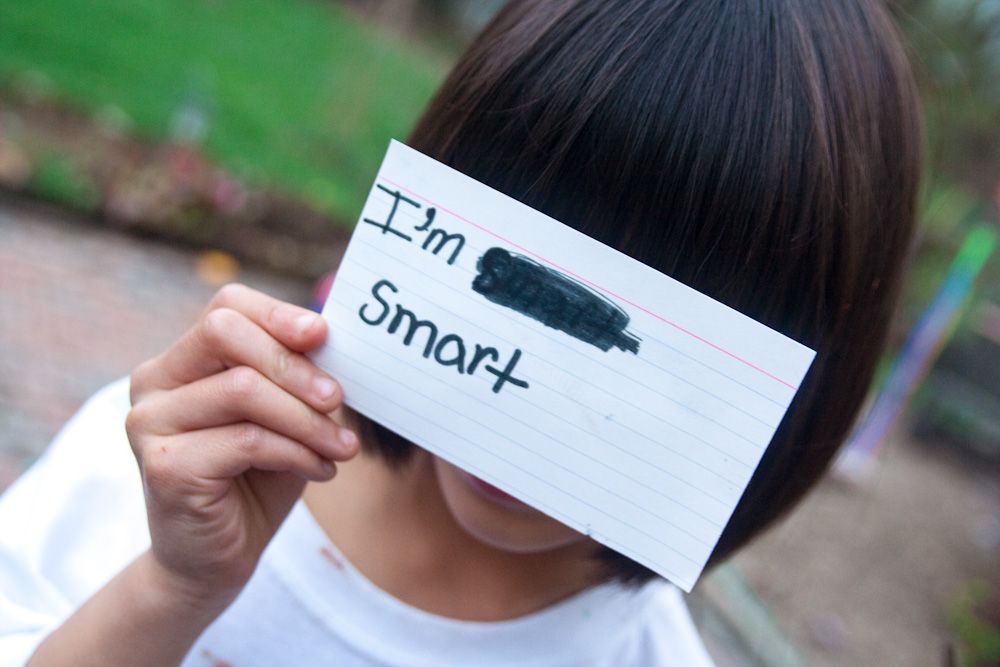 "a child holds a notecard in front of her face; the notecard reads ""I'm smart"" in black marker. ""Smart"" was written once, scratched out, written again."