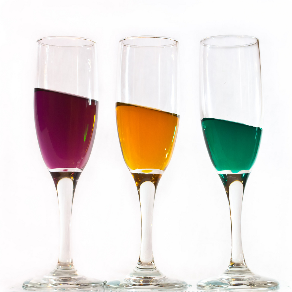 Three champagne glasses with red, orange, and green liquid inside. The liquid slants from top left to bottom right in a continuous line across the three glasses.