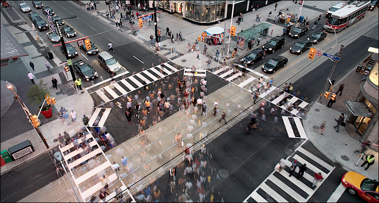 Busy intersection full of pedestrians crossing every which way. Pretty sure a few occupy the same space as each other.