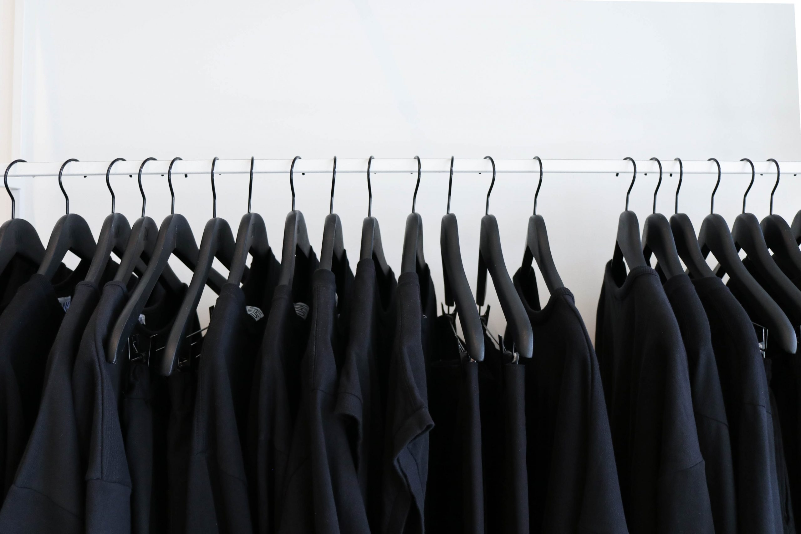 A row of pretty much identical black clothes hangs on a a rod. Gosh, which one should I pick this time?