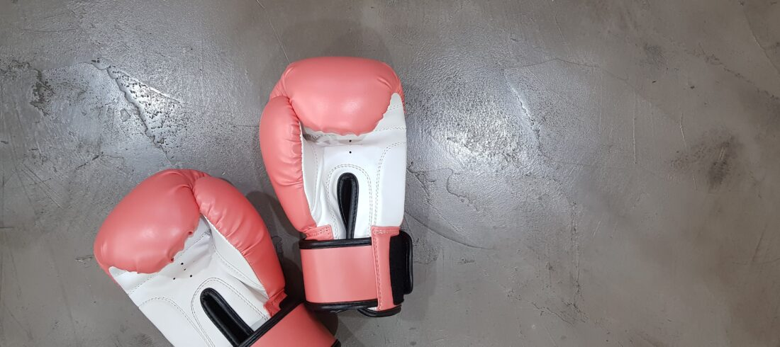 a pair of pink and white boxing gloves lie on a concrete surface