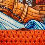 On the wall, a mural depicts a boat tossed by waves, struggling to lay anchor. In the front, a bold red couch rests comfortably, welcoming contemplation.