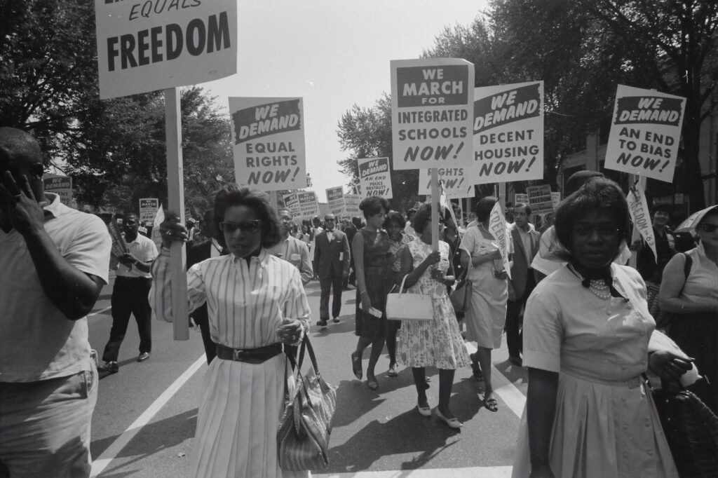 Photograph shows a procession of African Americans carrying signs for equal rights, integrated schools, decent housing, and an end to bias.