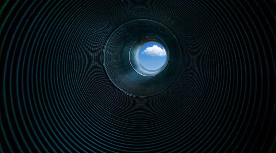 looking through a corrugated metal pipe toward a rich blue sky with white cloud in center of view