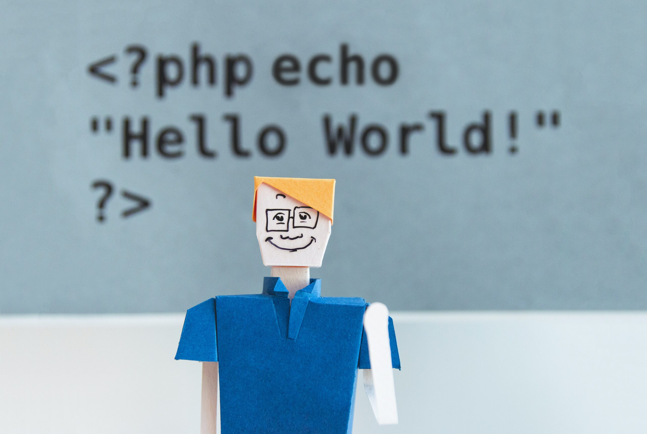 "paper figure of blond-haired white person in collared shirt and glasses waves at camera in front of ""Hello world"" echo statement written in PHP"