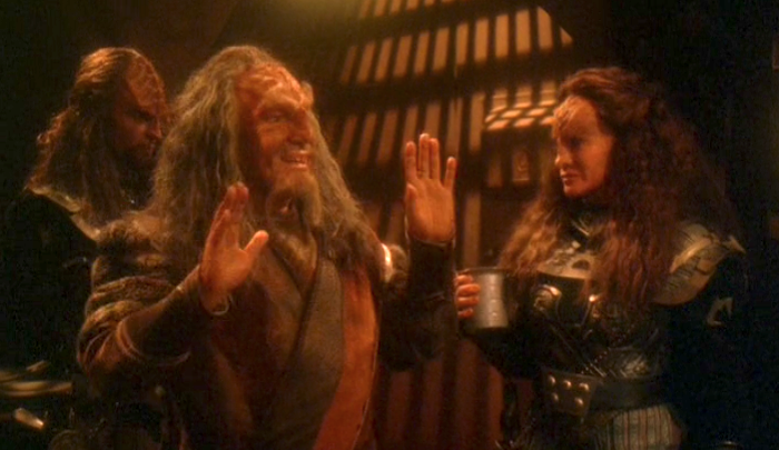Still taken from Star Trek episode, showing three Klingons in a dimly lit room. Character in foreground is smiling, accepting but downplaying acclaim from others off-screen.