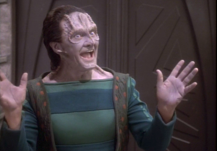 A wide-grinned alien in shirt and vest raises jazz hands to get you excited; he's probably trying to sell you something. Wait, it's Garak. He's definitely trying to sell you something.