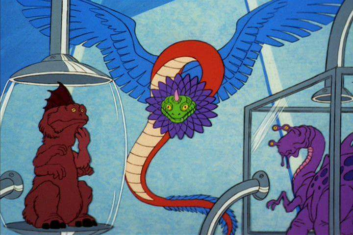 A winged, horned serpent hovers between two purple aliens in separate cages. Yes, it's as psychotic as it sounds.